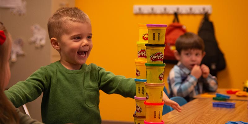 Boy stacking Play-Doh cans and smiling