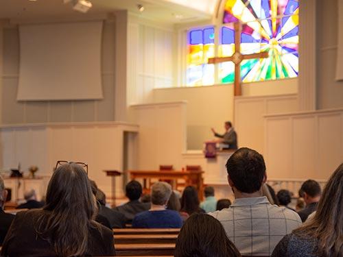People sitting in pews listening to sermon